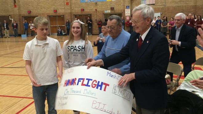 Ray Konkol , right, and Bill Jajewski receive a check for $1,000 from P.J. Jacobs Junior High School students Lydia Miller and Drew Harris for the Never Forgotten Honor Flight. Students at the school raised money to send the local veterans on the flight in April.