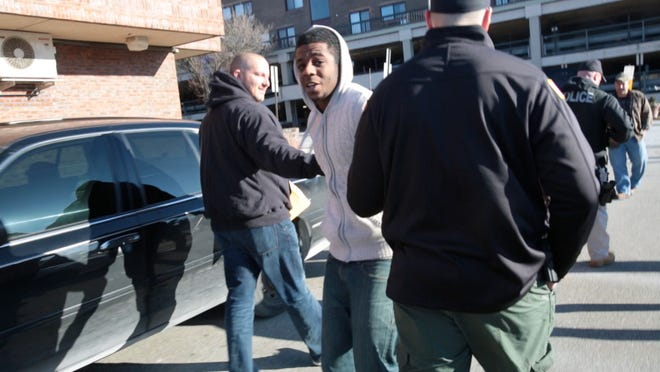 A suspect is led out of the Peekskill police department after a joint task force of federal, state and local law enforcement officers conducted raids throughout northern Westchester Jan. 13.