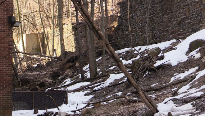 A view of the section of a 20 foot high retaining wall that collapsed and sent mud and uprooted trees onto the rear of 95-97 Walsh Road in Yonkers Wednesday.
