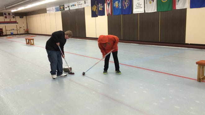Brian, 13, and Hunter, 11, Harms of Wisconsin Rapids, practice a curling technique known as sweeping Saturday, March 14, at the Tri-City Curling Club.