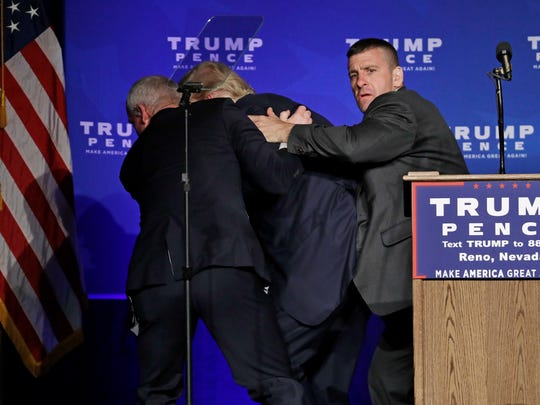 Secret Service agents rush Republican presidential candidate Donald Trump off the stage at a campaign rally in Reno, Nev., on Nov. 5, 2016.