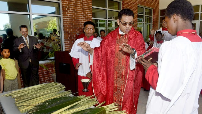 Rev. Lambert Lein bestows blessings onto the palms at the start of the Palm Sunday celebration at Holy Ghost Catholic Church in Opelousas.