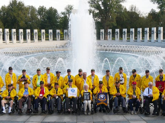 A group of World War II veterans pose for photo in front of the WWII Memorial in Washington D.C., during an Honor Flight of Southern New Mexico trip.