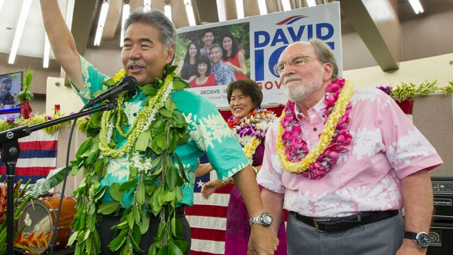 Hawaii State Sen. David Ige, right, waves to his supporters an thanks Hawaii Governor Neil Abercrombie, right, who promised his support Saturday, Aug. 9, 2014, in Honolulu. Ige defeated incumbent Hawaii Governor Neil Abercrombie in the state's primary election to win the Democratic Party's nomination. (AP Photo/Eugene Tanner) ORG XMIT: HIET109