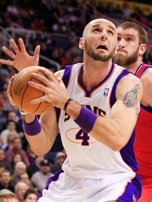 Phoenix Suns center Marcin Gortat looks to the basket past Philadelphia 76ers center Spencer Hawes during at US Airways in Phoenix, AZ.