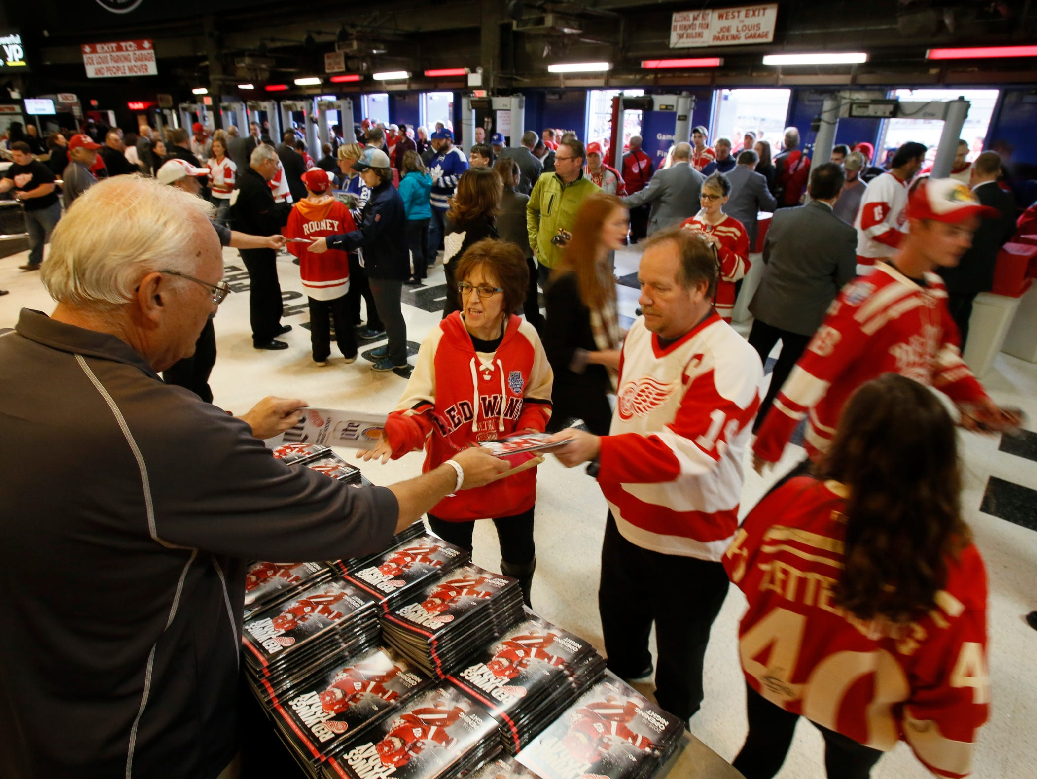 George Bresinsk, a volunteer for three years at Joe Louis Arena, hands out free programs to fans as they enter the Gordie Howe entrance for the Detroit Red Wings season opening game against the Toronto Maple Leafs on October 9, 2015, in Detroit.