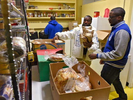 Phi Beta Sigma Fraternity members carry donated food