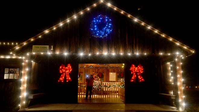 A visitor to Ft. St. Clair's Whispering Christmas takes a photograph inside a cabin Tuesday, Dec. 22, 2014, in Eaton, Ohio.
