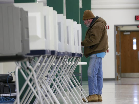 A person casts his vote on his ballot Tuesday, Feb.