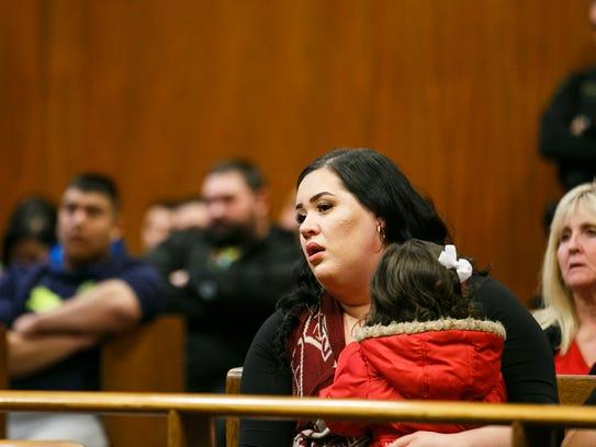 Marisela Garibay holds her daughter Mireya as she listens