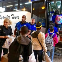 Alexandria Police Department officers tell D.F. Huddle Elementary top readers about activity bags they are taking with them on a reward field trip to New Orleans Thursday.