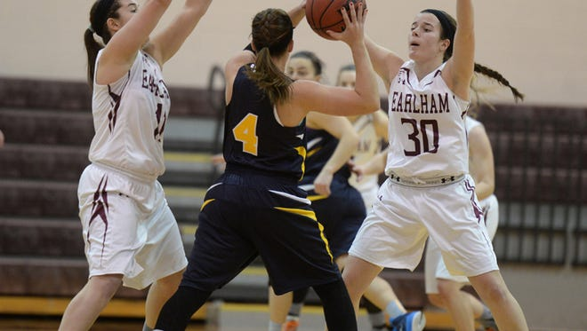 Earlham College's Kasin Spay, left, and Hannah Franklin defend against Mt. St. Joseph's Brilyn Webb during a basketball game at Earlham Saturday, Jan. 10, 2015.