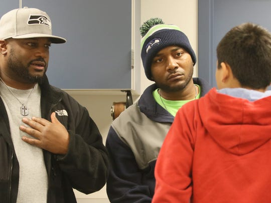 Volunteers Derrick Saulsberry Sr, left, and Keith Jackmon talk with Mountain View Middle School student Xavior Holliday during a mentoring class held at the school.