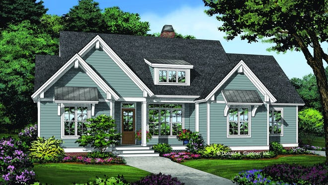 This cottage design welcomes you with large windows, wood siding, and metal roof details.