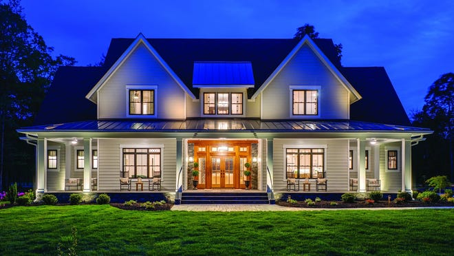 A wide front porch, metal roof, and double doors add classic curb appeal to this modern farmhouse design.