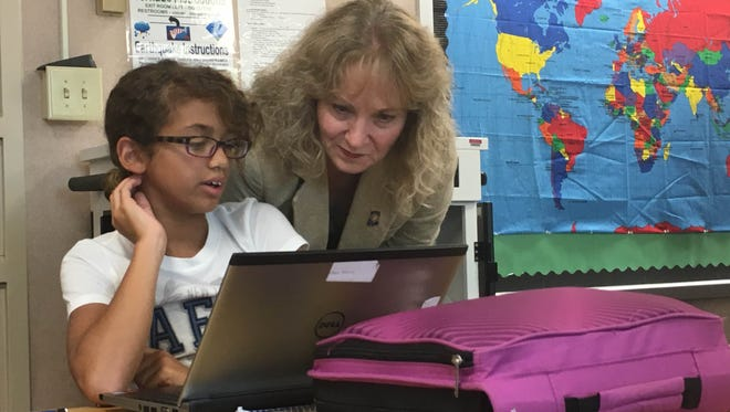 A sixth-grader at Northside Elementary School in Hartford City shows State Superintendent Glenda Ritz her online reading assignment during Ritz's visit Aug. 25. Ritz was recognizing the school for using formative data to assess students.