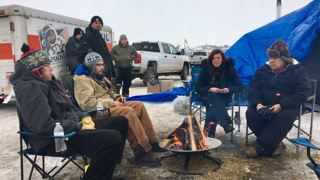 A group of Potawatomi tribe members from Michigan sits around a campfire Monday, Dec. 5, 2016 at the Oceti Sakowin Camp on the Standing Rock Indian Reservation in North Dakota. From left,  Dan Stohrer, 31, of Kalamazoo;  Norman Burfield, 25, of Niles; Michelle Thompson, 27, of Niles; and Donald Sumners, 61, of Dowagiac.