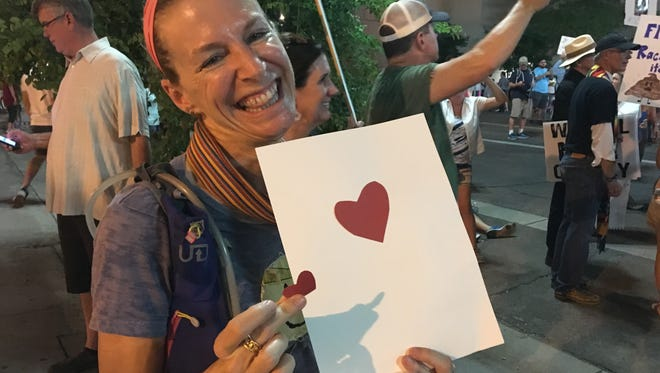 """Wendy White, a community health worker, handed out construction-paper hearts at the protest in downtown Phoenix on Aug. 22, 2017. """"Would you like a heart?"""" she would ask. No one turned her down."""