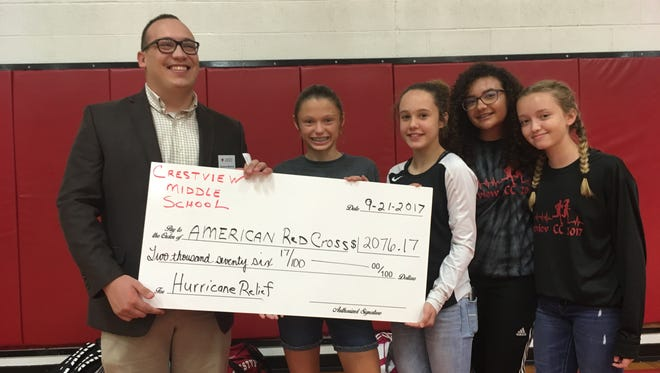 Zak McAvoy accepts a check from Crestview Middle School on behalf of American Red Cross for hurricane relief efforts. Pictured with McAvoy are eighth graders Morgan Welch, Skylar Ramsay, Bridgette Bays and Holly Collett.