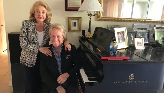 Peggy Cravens, Chairman of the Board of the Virginia Waring International Piano Competition and pianist/composer John Bayless, artistic director for the Waring, pose beside Bayless' grand piano at his Desert Island residence in Rancho Mirage on Sept. 15, 2017.