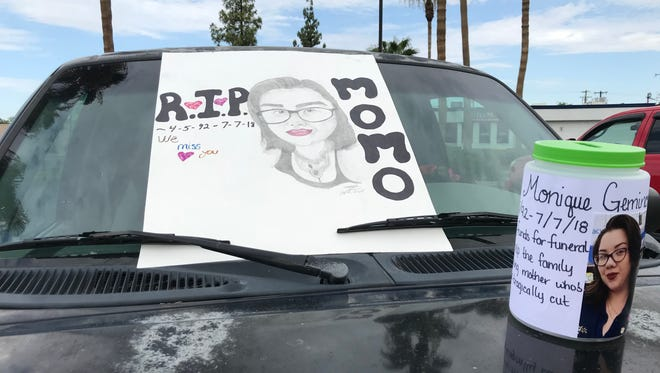 A sign and fundraiser container sit on the hood of Monique Gemino's car on July 14, 2018. Phoenix police say Gemino's ex-boyfriend, Luis Madrigal, beat her to death with a tire iron.
