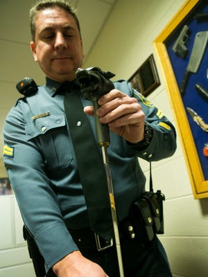 Delaware Capitol Police Cpl. Jeffry Oldham shows a walking cane that has a hidden sword inside. Security at the New Castle Courthouse confiscate a variety of dangerous items on a regular basis.