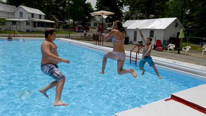 Ashton Weber, 12, left, Grace Gahm, 13, center, and Josiah Gahm, 11, jump into the Copeland Swimming Pool at the Lancaster Camp Ground in Lancaster. The pool, which had been closed for about two years reopened over the weekend. It is open to the public with either a daily or season passes.