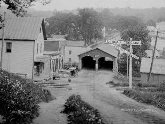 The two-lane covered bridge, unique in its time dominated Bridge Street. Built by the town around 1835, the bridge planner desired a structure that would allow a full load of hay to pass under it and wide enough so that livestock would have no problems going through it. The other two-lane covered bridges surviving are the the Pulp Mill Bridge between Weybridge and Middlebury and  the one at the Shelburne Museum that  until recently served as its entryway.