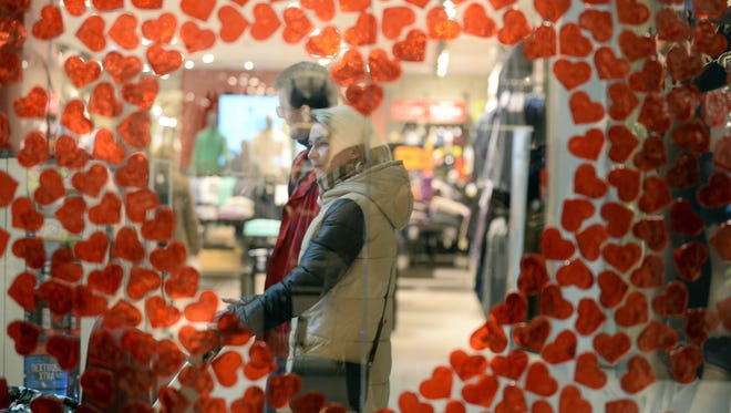 A couple is seen though the Valentine's Day  decorated window of a shop in Warsaw, Poland, February 13, 2015.
