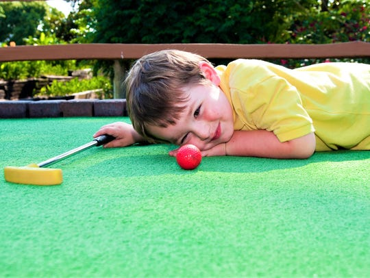 A young boy plays mini golf on putt-putt course.