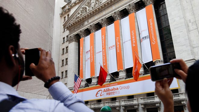 People take photographs of the New York Stock Exchange on the day of Alibaba's initial public offering, Sept. 19, 2014, in New York.