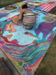 """Raechel Schultz of Wausau works on her drawing based on the book """"Where The Wild Things Are,"""" by Maurice Sendak at 2011's Chalkfest event."""