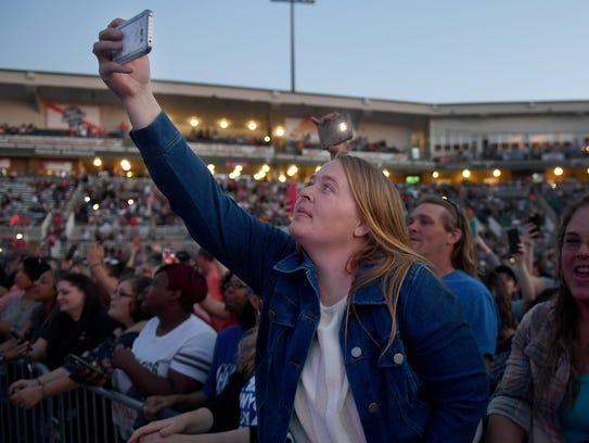 Casandra Simpson reaches her phone up to take photos