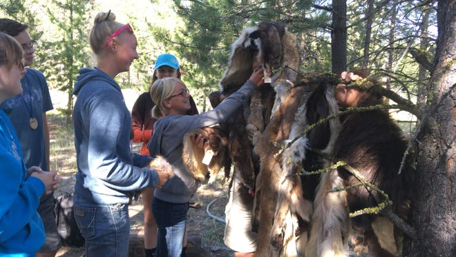 While campers grin at the sight, Abby Hutton drapes a camper with a variety of wildlife pelts during the range and wildlife class at Montana Natural Resources Youth Camp. Teens enjoy a week of learning how and why to manage soil, water, rocks, range and wildlife to keep resources healthy and productive.