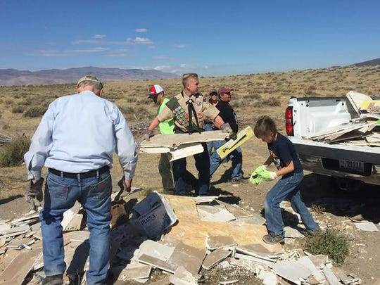 Eagle Scout candidate Steven Schroetlin and others cleaning up a pile of sheet rock.