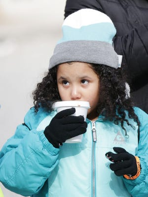 Kylie Nicholson, 6, of Eastpointe stays warm with her mother Jovaughn Nicholson at the Meridian Winter Blast.