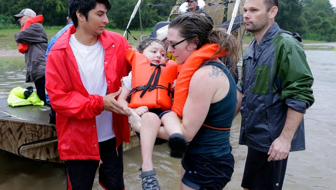 Mindy Walker and her three year old son Connor Martinez are helped out of a boat after being rescued from their home along Cypress Creek at Kuykendal 15 miles northwest of downtown Houston, Texas on Aug. 28, 2017. The areas in and around Houston and south Texas are experiencing record floods after more than 24 inches of rain after Harvey made landfall in the south coast of Texas as a category 4 hurricane, the most powerful to affect the US since 2004. Harvey has weakened and been downgraded to a tropical storm and is expected to cause heavy rain for several days.