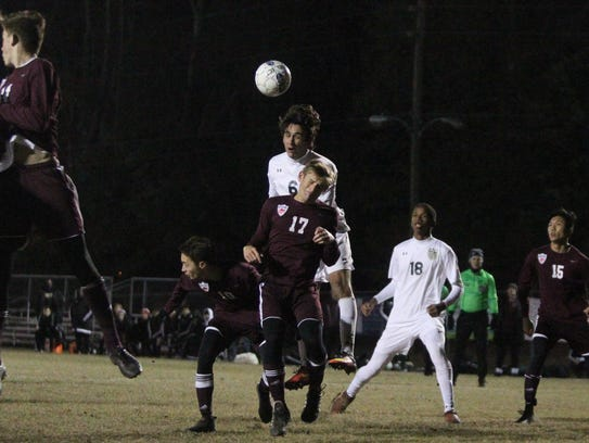 Lincoln's Gavin Mott-Smith goes up for a header off