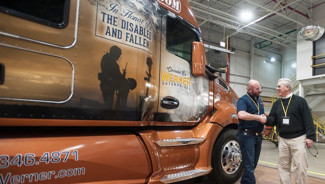 Troy Davidson, left, shakes Congressman Brad Wenstrup's hand, right, during the Kenworth Hiring our Heroes event on Jan. 24, 2017, in Chillicothe, Ohio. Davidson, a Navy veteran, was the 2016 winner of a new truck that is given to veterans in the Hiring our Heroes program by Kenworth.