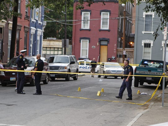 Cincinnati Police investigate the scene of a shooting on Neave Street just north of the intersection of Storrs Street in Lower Price Hill Wednesday June 18, 2014.  One person was transported to University Hospital.