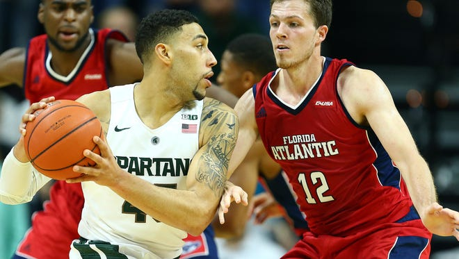 Michigan State guard Denzel Valentine (45) is defended by Florida Atlantic guard Jackson Trapp (12) during the first half of a game at Jack Breslin Student Events Center.
