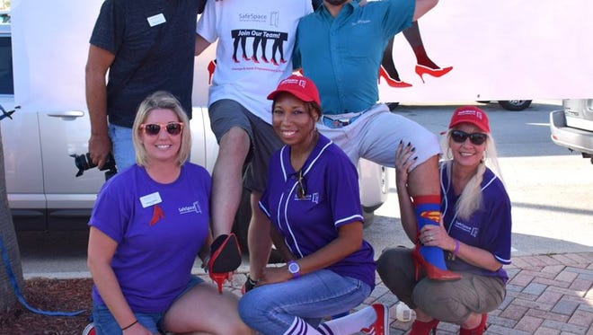 Juliana Walker (front, from left), Lewana Dupree, Melissa Zolla, and Mitch Kloorfain (back, from left), Indian River County Sheriff's Office Lt Eric Flowers, and Pete Morello attend SafeSpace's Walk a Mile in Her Shoes event Oct. 15 in downtown Fort Pierce.