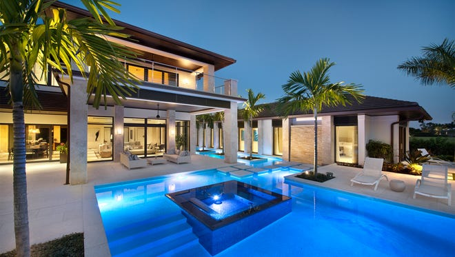 This Harwick Home custom built house makes a C-shape to surround this luxurious pool and patio.