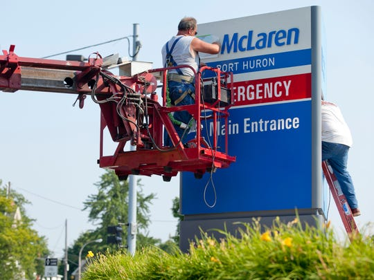 Workers replace a Port Huron Hospital sign with a new