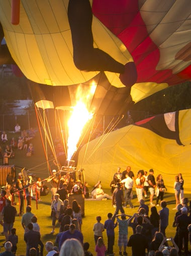 People gather around a balloon while the envelope is filled with fire during the Cave Creek Balloon Festival, Saturday, May, 23, 2015, in Cave Creek, Ariz.