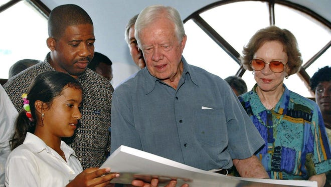 """Former President Jimmy Carter and his wife Rosalynn, right, receive a drawing as a gift from Nudersi Garcia, 15, left, a patient at the """"Los Cocos"""" AIDS sanatorium during his visit to the medical facility in Havana, Cuba, in 2001. Carter and his wife are known for their humanitarian work."""