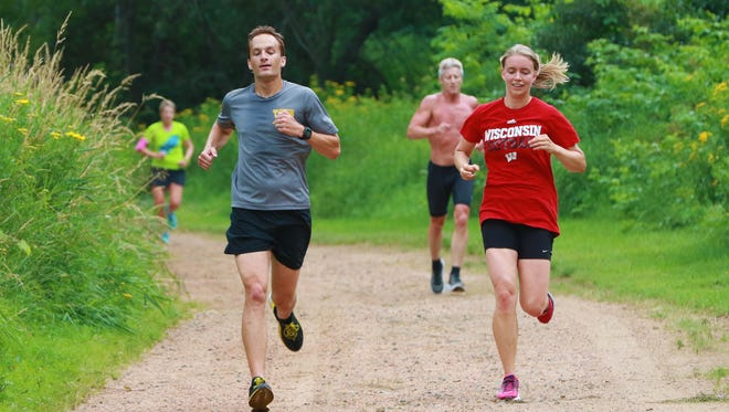 Kris Borchardt (left, gray shirt), a founder of the Wausau Area Striders running club, leads a group of runners in a hill workout at Sylvan Hill Park.