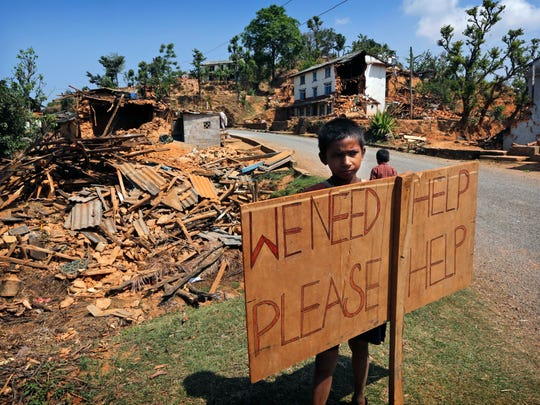 A Nepalese boy stands outside his village with a signboard