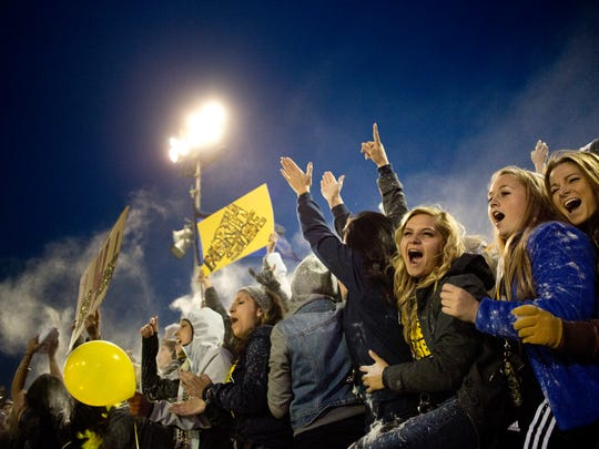Port Huron Northern students cheer and throw baby powder in the air as the team takes the field during the Crosstown Showdown Friday, October 23, 2015 at Memorial Stadium in Port Huron.