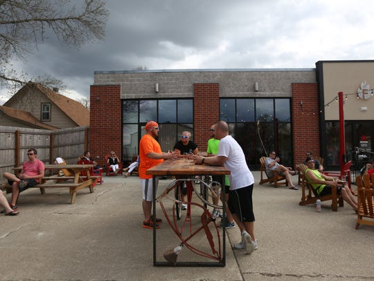 A group of bikers relax on the patio of Firetrucker